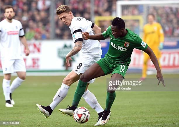 Mike Frantz of SC Freiburg challenges Abdul Rahman Baba of FC Augsburg during the Bundesliga match between SC Freiburg and FC Augsburg at...