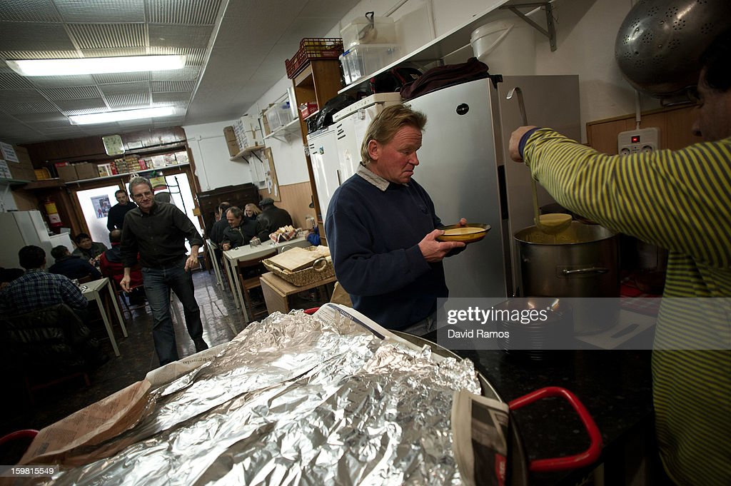 Mike from Germany, 46, serves soup and paella to needy people at the 'El Chiringuito de Dios' ('The Stall of God') on January 10, 2013 in Barcelona, Spain. The German pastor Wolfgang Striebinger has lived in Barcelona since 1991, originally employed to minister to youths during the Barcelona Olympic Games, he decided to stay and since 2000 has run 'El Chinguito de Dios' (The Stall of God). In his mission to support the homeless, Wolfgang and his volunteers offer a place for up to 200 people to come and have some food daily and also offering them assistance with grooming and clothes. Many of the volunteers are homeless and help out in return for meals and a bed. Wolfgang's ethos is to provide peace, calm and dignity to all those that need it amongst Barcelona's burgeoning homeless population. Due to the economic situation his doors are now also open to the long term unemployed and families with little or no income. According to the latest figures 21.8% of the Spanish populations are living below the poverty line.