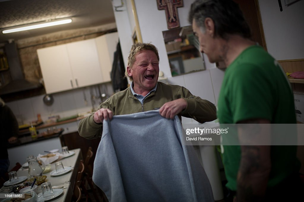 Mike from Germany, 46, shares a joke at the 'El Chiringuito de Dios' ('The Stall of God') on January 10, 2013 in Barcelona, Spain. Mike arrived to spain 17 years ago living on the streets many of them. He has only the last year of Medicine to finish the career and he use to work every summer helping at the Hospital del Mar of Barcelona as medical examiner. He is a volunteer of the 'El Chiringuito de Dios' for 6 months. The German pastor Wolfgang Striebinger has lived in Barcelona since 1991, originally employed to minister to youths during the Barcelona Olympic Games, he decided to stay and since 2000 has run 'El Chinguito de Dios' (The Stall of God). In his mission to support the homeless, Wolfgang and his volunteers offer a place for up to 200 people to come and have some food daily and also offering them assistance with grooming and clothes. Many of the volunteers are homeless and help out in return for meals and a bed. Wolfgang's ethos is to provide peace, calm and dignity to all those that need it amongst Barcelona's burgeoning homeless population. Due to the economic situation his doors are now also open to the long term unemployed and families with little or no income. According to the latest figures 21.8% of the Spanish populations are living below the poverty line.