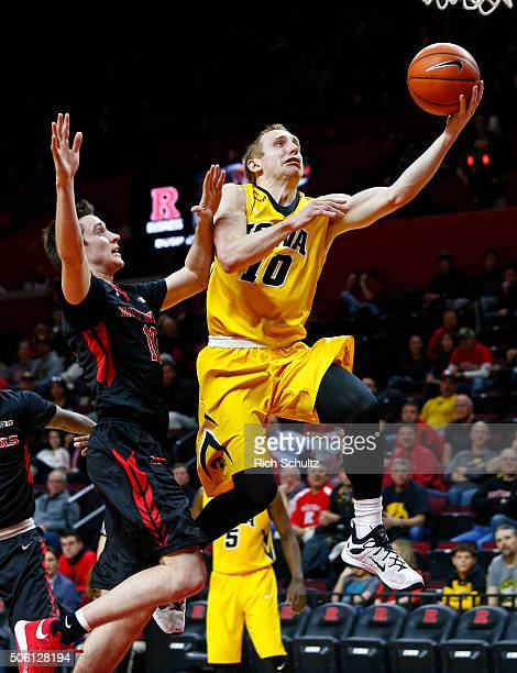 Mike Gesell of the Iowa Hawkeyes attempts a layup as Justin Goode of the Rutgers Scarlet Knights defends during the first half of a college...
