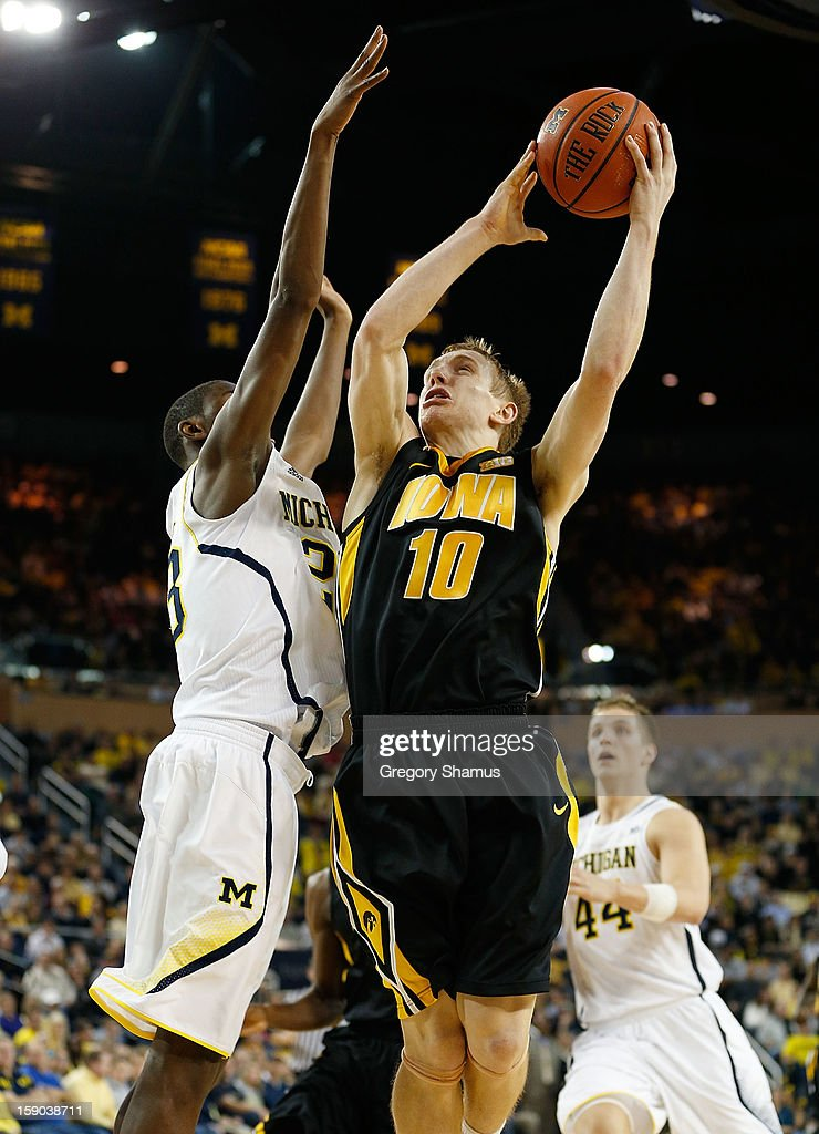 Mike Gesell #10 of the Iowa Hawkeyes tries to get a second half shot off over Caris LeVert #23 of the Michigan Wolverines at Crisler Center on January 6, 2013 in Ann Arbor, Michigan. Michigan won the game 95-67.