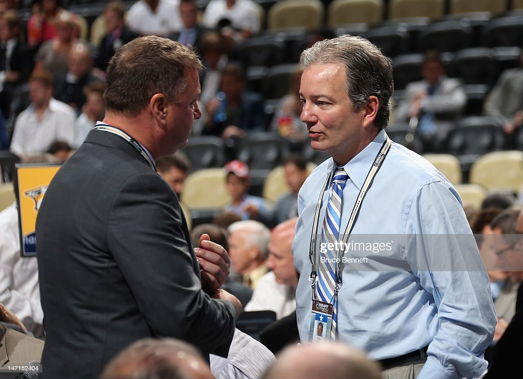 Mike Gillis of the Vancouver Canucks and Ray Shero of the Pittsburgh Penguins discuss matters during Round One of the 2012 NHL Entry Draft at Consol Energy Center on June 22, 2012 in Pittsburgh, Pennsylvania.
