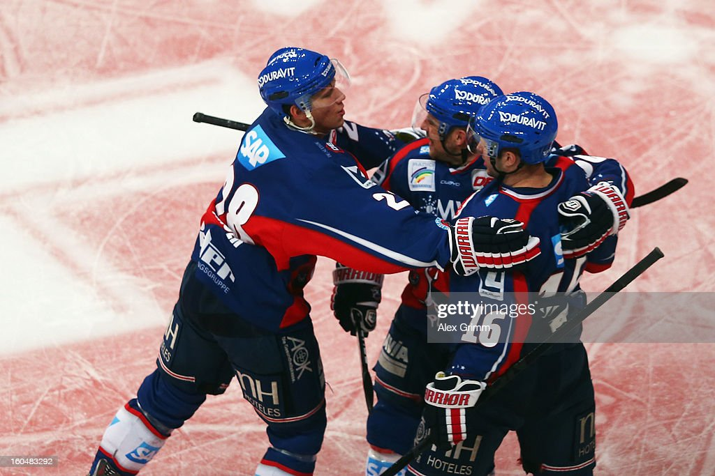 Mike Glumac (R) of Mannheim celebrates his team's first goal with team mates during the DEL match between Adler Mannheim and Eisbaeren Berlin at SAP Arena on February 1, 2013 in Mannheim, Germany.