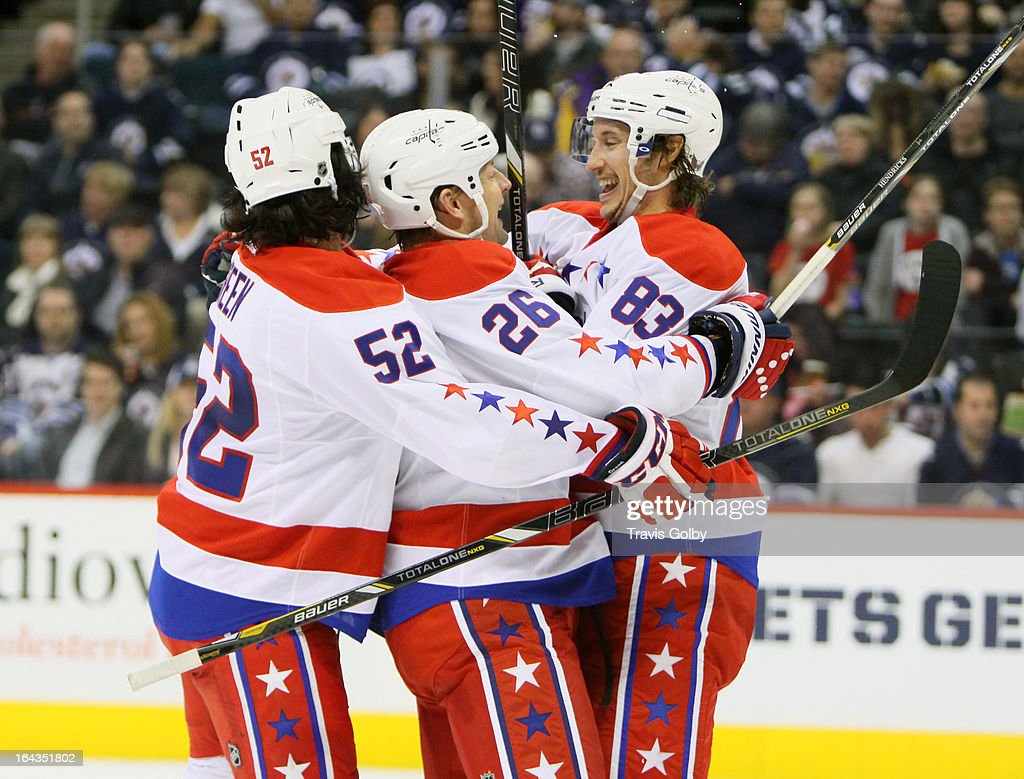 Mike Green #52, Matt Hendricks #26 and Jay Beagle #83 of the Washington Capitals celebrate a second-period goal against the Winnipeg Jets at the MTS Centre on March 22, 2013 in Winnipeg, Manitoba, Canada.
