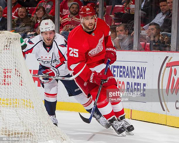 Mike Green of the Detroit Red Wings skates around the net in front of Evgeny Kuznetsov of the Washington Capitals during an NHL game at Joe Louis...