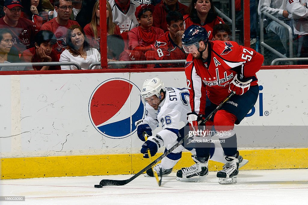 Mike Green #52 of the Washington Capitals and <a gi-track='captionPersonalityLinkClicked' href=/galleries/search?phrase=Martin+St.+Louis&family=editorial&specificpeople=202067 ng-click='$event.stopPropagation()'>Martin St. Louis</a> #26 of the Tampa Bay Lightning battle for the puck during an NHL game at Verizon Center on April 7, 2013 in Washington, DC.
