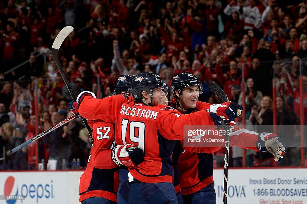 Mike Green #52 of the Washington Capitals celebrates with teammates after scoring a goal in the third period during an NHL game against the Vancouver Canucks at Verizon Center on March 14, 2014 in Washington, DC.