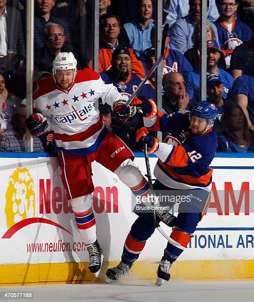 Mike Green of the Washington Capitals is checked by Josh Bailey of the New York Islanders during the first period in Game Four of the Eastern...