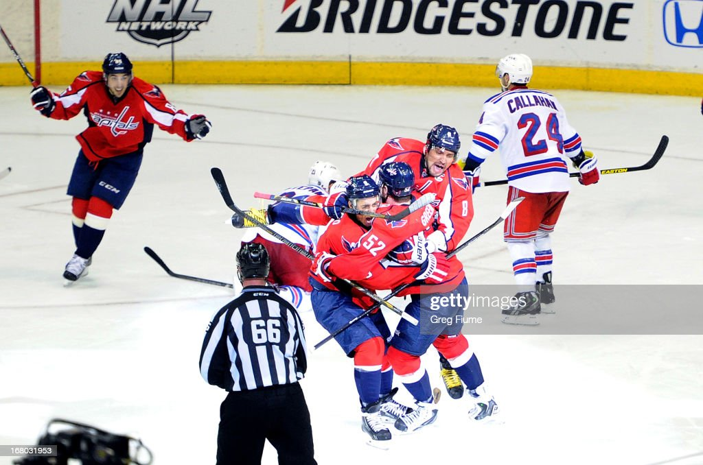Mike Green of the Washington Capitals is mobbed by Mike Ribeiro and Alex Ovechkin after scoring the game winning goal against the New York Rangers in...