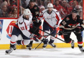 Mike Green of the Washington Capitals knocks the puck down with his hand as Erik Condra of the Ottawa Senators chases during an NHL game at Canadian...