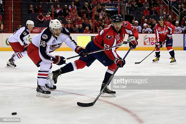 Mike Green of the Washington Capitals passes the puck behind Boone Jenner of the Columbus Blue Jackets during the second period at Verizon Center on...