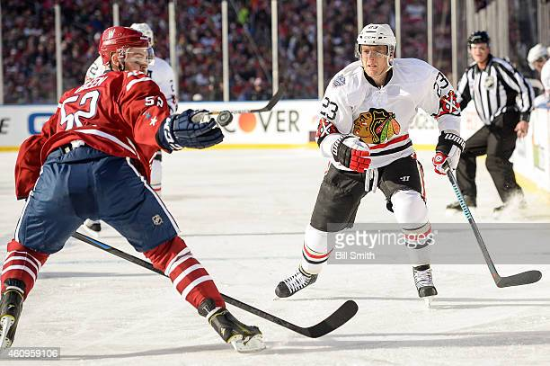 Mike Green of the Washington Capitals reaches for the puck next to Kris Versteeg of the Chicago Blackhawks during the 2015 Bridgestone NHL Winter...