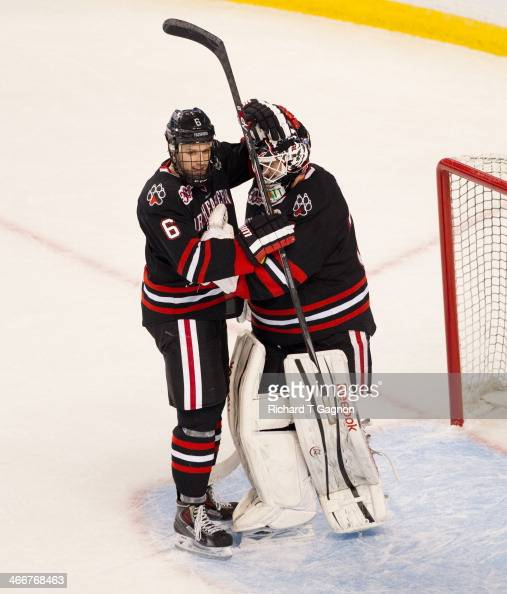 Mike Gunn of the Northeastern University Huskies congratulates teammate Clay Witt on his shutout against the Harvard Crimson NCAA hockey action in...
