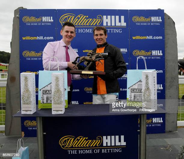 Mike Hall from William Hill presents Richard Johnson with his trophy after victory on Teak in the William Hill 80th Anniversary Handicap Hurdle at...