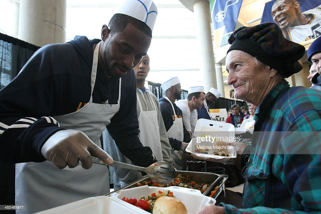 Mike Harris #33 of the Utah Jazz dishes out food during the we care-we share Thanksgiving Dinner feeding the homeless at EnergySolutions Arena on November 27, 2013 in Salt Lake City, Utah.