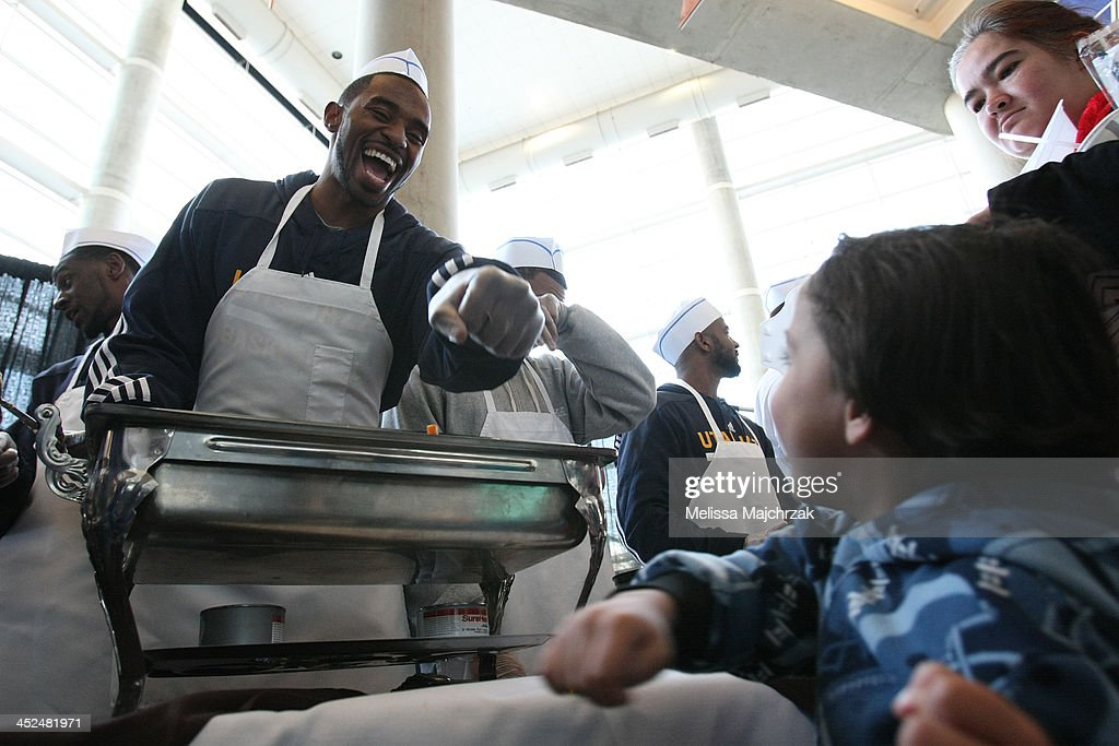 Mike Harris #33 of the Utah Jazz laughs with a fan during the we care-we share Thanksgiving Dinner feeding the homeless at EnergySolutions Arena on November 27, 2013 in Salt Lake City, Utah.