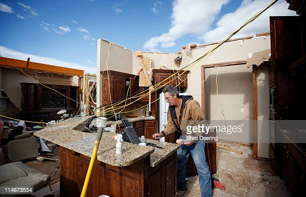Mike Hartman cleans up his kitchen after his house was struck by a tornado May 25 2011 in Piedmont Oklahoma The state medical examiner's office said...