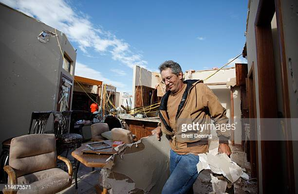 Mike Hartman hauls wet sheetrock out of his kitchen after his house was struck by a tornado May 25 2011 in Piedmont Oklahoma The state medical...