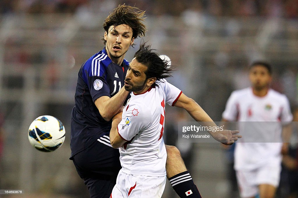 Mike Havenaar of Japan and Shadi Abu Hashhash of Jordan compete for the ball during the FIFA World Cup Asian qualifier match between Jordan and Japan at King Abdullah International Stadium on March 26, 2013 in Amman, Jordan.