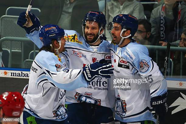 Mike Hedden of Straubing celebrates his team's third goal with team mates Dylan Yeo and Steven Zalewski of Straubing during the DEL match between...