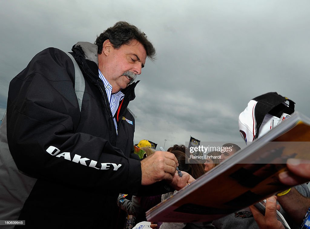 Mike Helton, President of NASCAR, signs autographs prior to the NASCAR Sprint Cup Series Geico 400 at Chicagoland Speedway on September 15, 2013 in Joliet, Illinois.