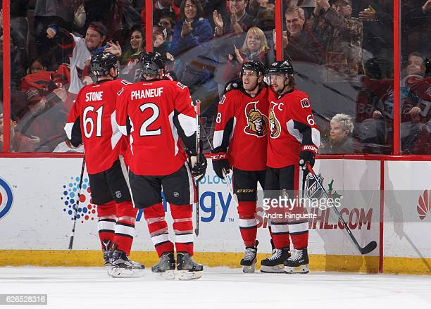 Mike Hoffman of the Ottawa Senators celebrates his second period goal against the Buffalo Sabres with teammates Mark Stone Dion Phaneuf and Erik...