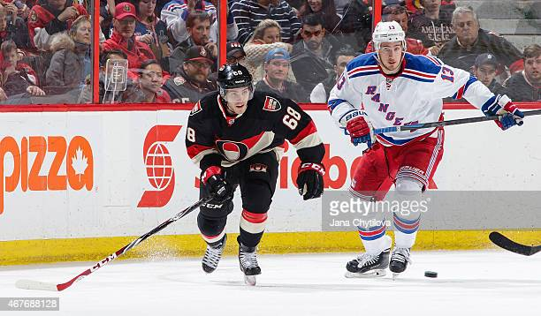 Mike Hoffman of the Ottawa Senators skates against Kevin Hayes of the New York Rangers for the puck at Canadian Tire Centre on March 26 2015 in...