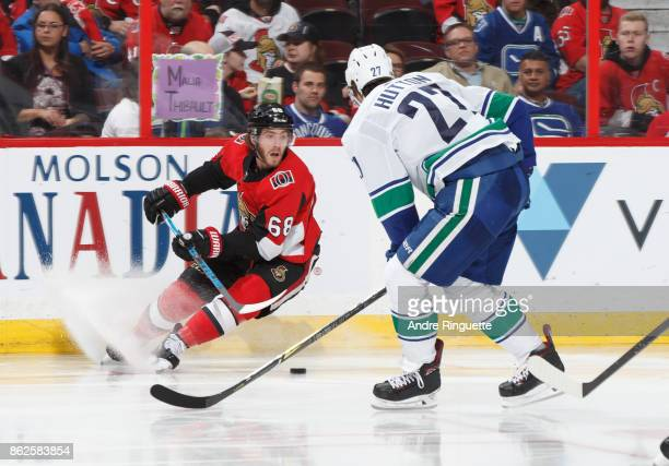 Mike Hoffman of the Ottawa Senators stickhandles the puck against Ben Hutton of the Vancouver Canucks at Canadian Tire Centre on October 17 2017 in...