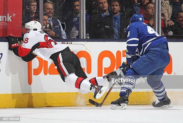 Mike Hoffman of the Ottawa Senators takes a big hit into the boards from Roman Polak of the Toronto Maple Leafs during an NHL game at the Air Canada...