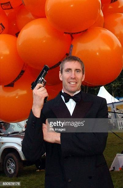 Mike Howard dressed as James Bond before taking to the sky dangling beneath hundreds of helium filled balloons from the Bristol Balloon Fiesta *...
