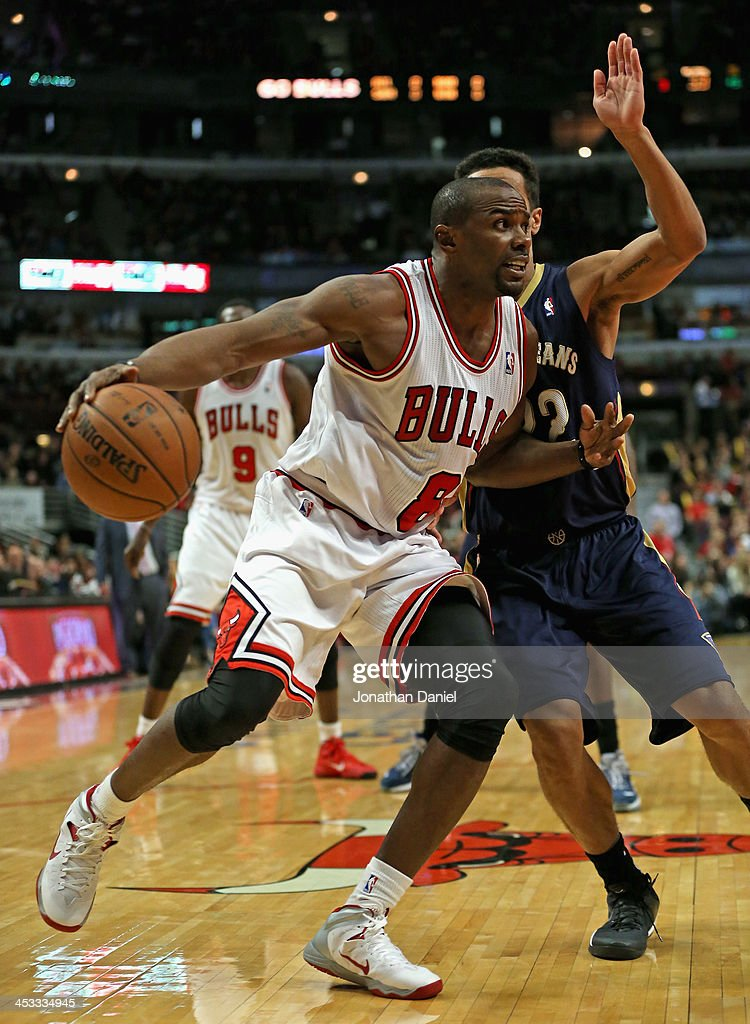 Mike James #8 of the Chicago Bulls moves past Brian Roberts #22 of the New Orleans Pelicans at the United Center on December 2, 2013 in Chicago, Illinois. The Pelicans defeated the Bulls 131-128 in triple overtime.