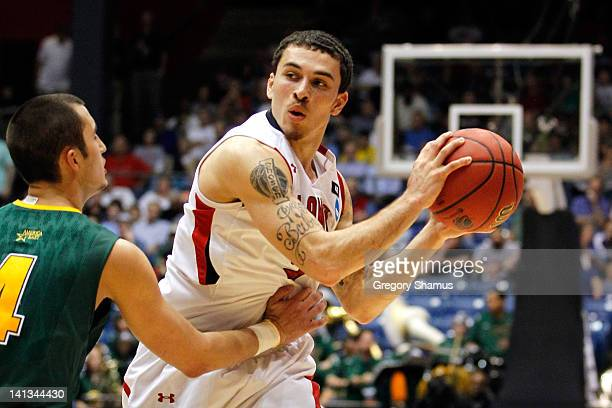 Mike James of the Lamar Cardinals looks to pass against Four McGlynn of the Vermont Catamounts in the first round of the 2011 NCAA men's basketball...