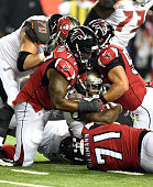 Mike James of the Tampa Bay Buccaneers is tackled by Ra'Shede Hageman Paul Worrilow and Kroy Biermann of the Atlanta Falcons at the Georgia Dome on...