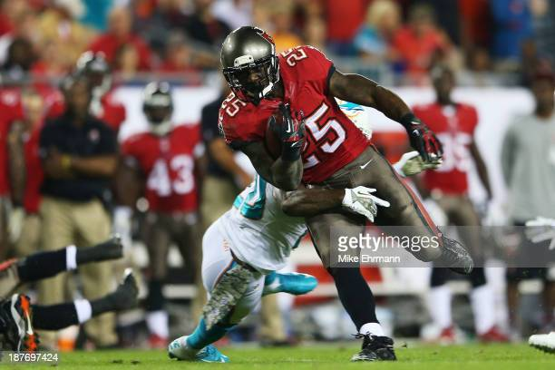 Mike James of the Tampa Bay Buccaneers tries to break the tackle of Reshad Jones of the Miami Dolphins in the first quarter at Raymond James Stadium...