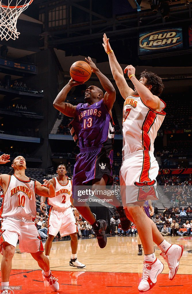 Mike James of the Toronto Raptors goes to the basket past Zaza Pachulia of the Atlanta Hawks during the game at Philips Arena on December 2 2005 in...