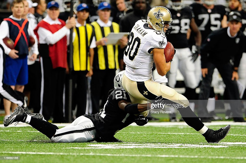 Mike Jenkins #21 of the Oakland Raiders tackles <a gi-track='captionPersonalityLinkClicked' href=/galleries/search?phrase=Jimmy+Graham&family=editorial&specificpeople=834247 ng-click='$event.stopPropagation()'>Jimmy Graham</a> #80 of the New Orleans Saints during a preseason game at the Mercedes-Benz Superdome on August 16, 2013 in New Orleans, Louisiana.