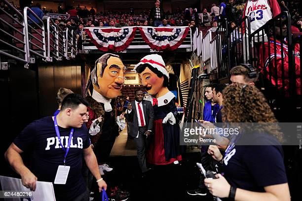 Mike Johnson a media relations intern with the Phoenix Suns splits between caricature costumes of Ben Franklin and Betsy Ross before the start of the...
