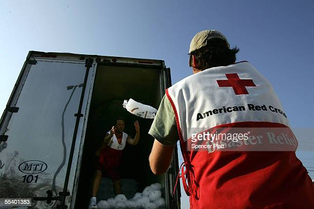 Mike Johnson a volunteer with the American Red Cross unloads bags of ice for people in need after Hurricane Katrina September 14 2005 in Biloxi...