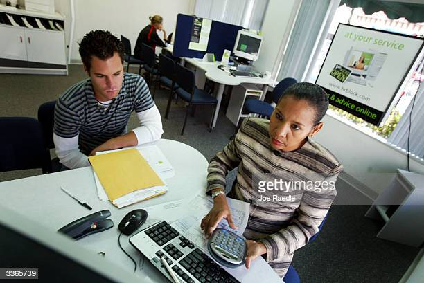 Mike Johnson gets help with his taxes from tax specialist Deliana Jarquin April 14 2004 at HR Block in Coral Gables Florida With only one day to go...