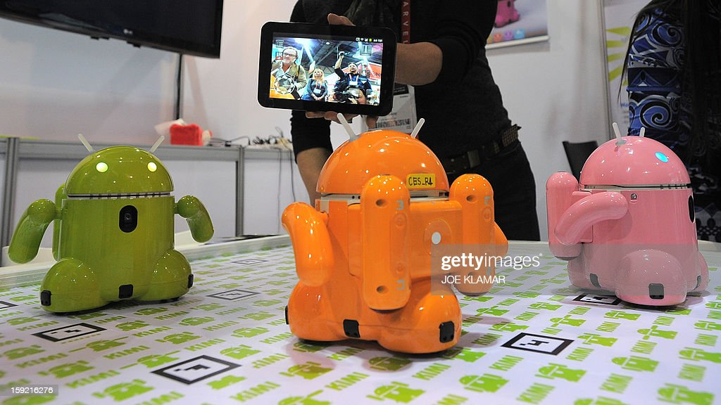 Mike Kim from Korea's Roboware operates smart device controlled toy robots are displayed at the 2013 International CES at the Las Vegas Convention Center on January 9, 2013 in Las Vegas, Nevada. CES, the world's largest annual consumer technology trade show, runs from January 8-11 and is expected to feature 3,100 exhibitors showing off their latest products and services to about 150,000 attendees.