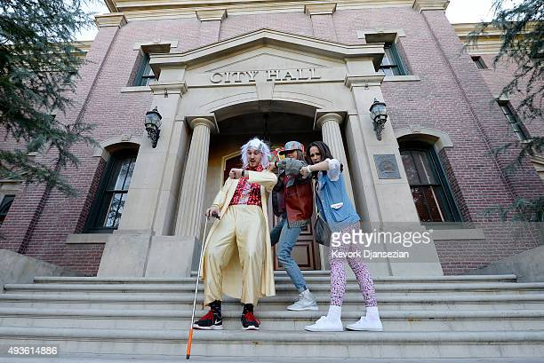 Mike Knell dressed as the character Dr Emmett Brown Stephanie Knell and Jackie Peters pose on steps of Hill Valley Courthouse Square in the back lot...