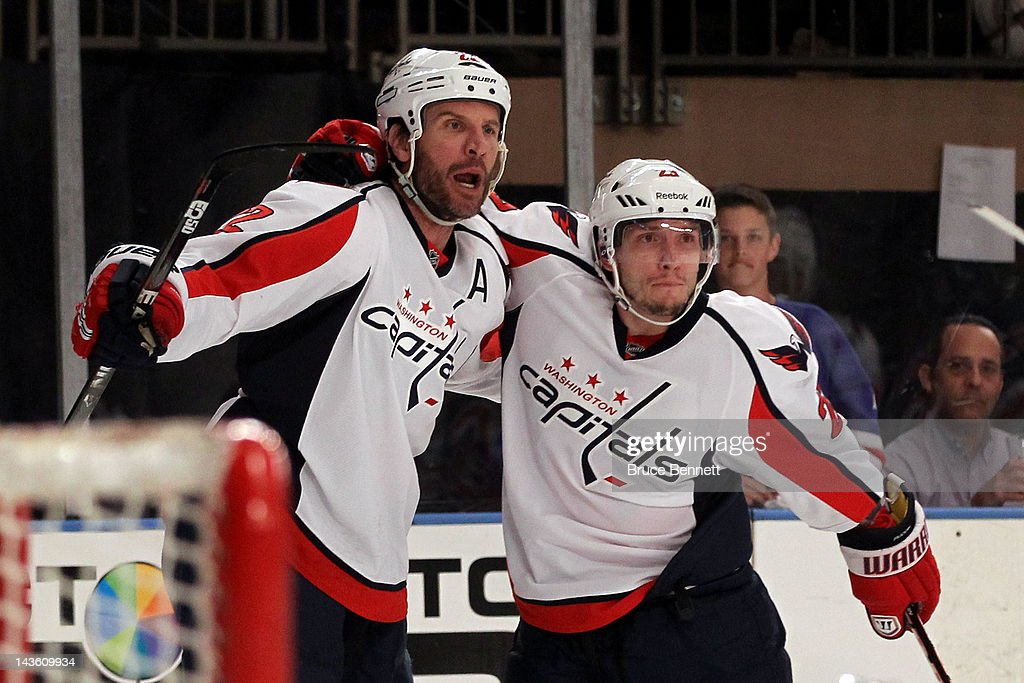 Mike Knuble #22 oand Keith Aucoin #23 of the Washington Capitals celebrate after Knuble scored a first period goal against the New York Rangers in Game Two of the Eastern Conference Semifinals during the 2012 NHL Stanley Cup Playoffs at Madison Square Garden on April 30, 2012 in New York City.