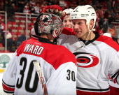 Mike Komisarek of the Carolina Hurricanes congratulates teammate Cam Ward after an NHL game against the Detroit Red Wings on April 11 2014 at Joe...