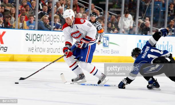 Mike Komisarek of the Montreal Canadiens controls the puck past Jeff Halpern of the Tampa Bay Lightning at the St Pete Times Forum on December 30...