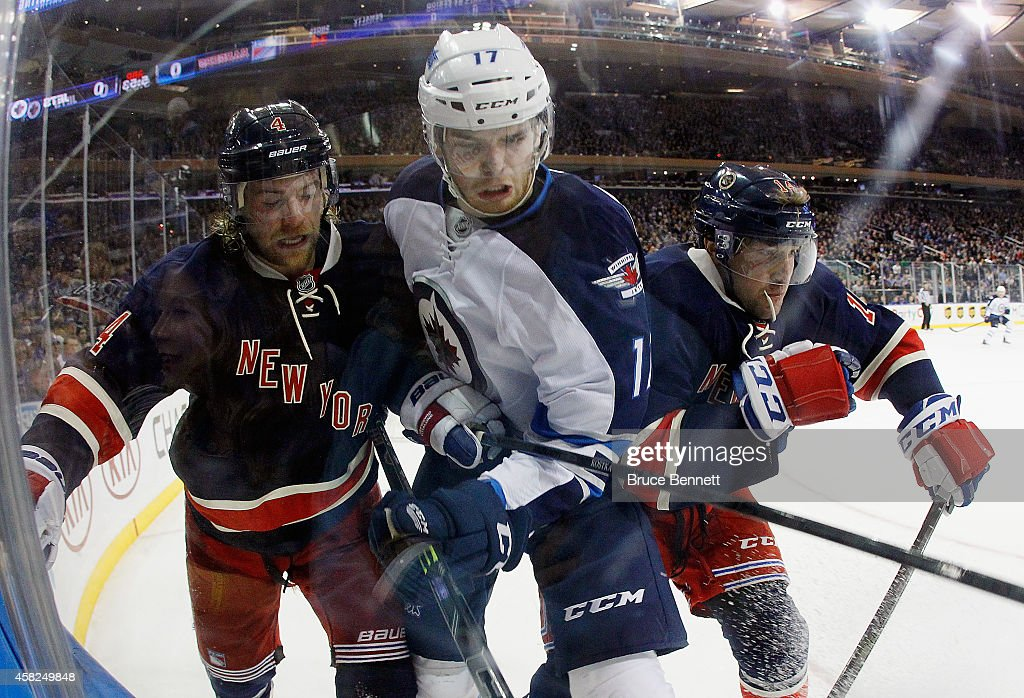 Mike Kostka and Chris Mueller of the New York Rangers combine to hit Adam Lowry of the Winnipeg Jets at Madison Square Garden on November 1 2014 in...