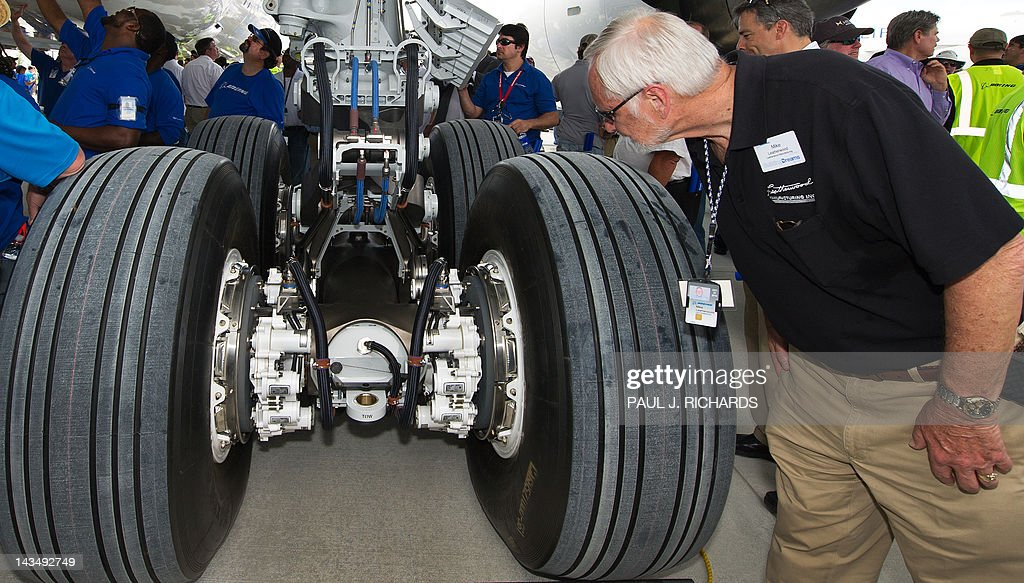 Mike Leatherwood (R), from Leatherwood Manufacturing, looks over the landing gear area on the new Boeing 787 Dreamliner built for Air India with other employees and contractors after it was rolled off the production line at Boeing's new production facilities April 27, 2012, in North Charlston, South Carolina. The plane marks Boeing's first South Carolina made 787 Dreamliner aircraft. AFP PHOTO/Paul J. Richards