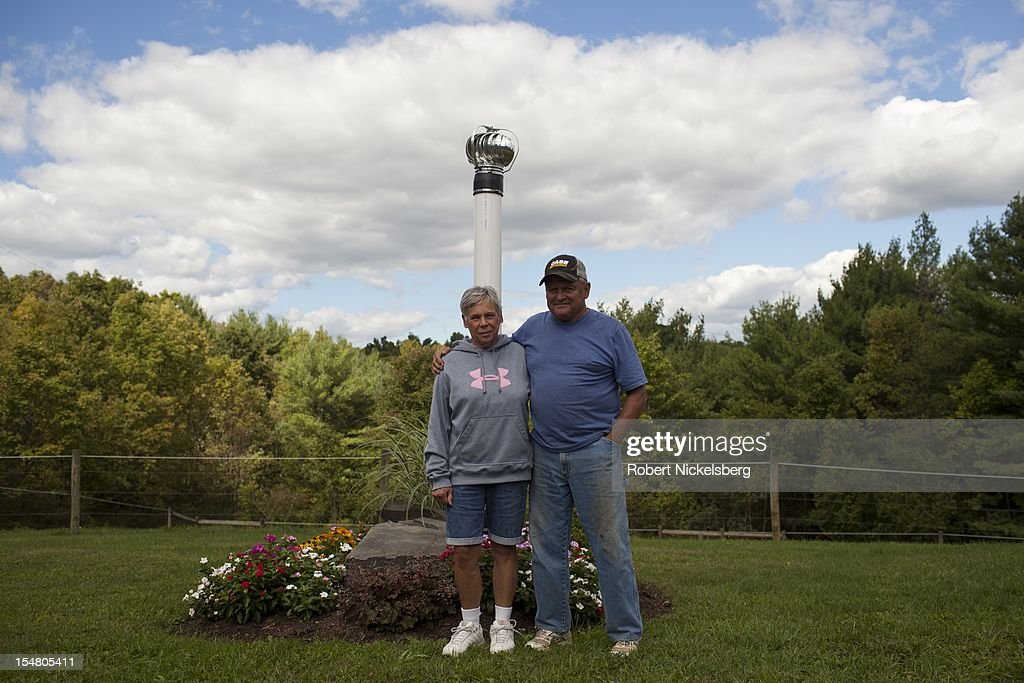 Mike Leighton, 68 years, and his wife, stand next to a venting pipe for their contaminated water well September 10, 2012 at his home in Granville Summit, Pennsylvania. Leighton's water well was contaminated by methane released from a hydrofracked gas well drilled by the Chesapeake Energy in May 2012. Chesapeake has supplied Creighton's home with a water filtration system and delivers drinking water. Methane gas from the fracked well is also leaking into his basement for which Chesapeake provides a vacuum pump. Leighton and his wife built their retirement home on 10-acres of land which sits above the Marcellus Shale gas field. Hydrofracking is a controversial drilling method which pumps millions of gallons of water, sand and chemicals into horizontally drilled wells to stimulate the release of the gas. The Marcellus Shale gas field stretches diagonally across West Virginia, Ohio, Pennsylvania and New York State. Hydrofracking's environmental impact is a politically sensitive issue in a resource dependent state.
