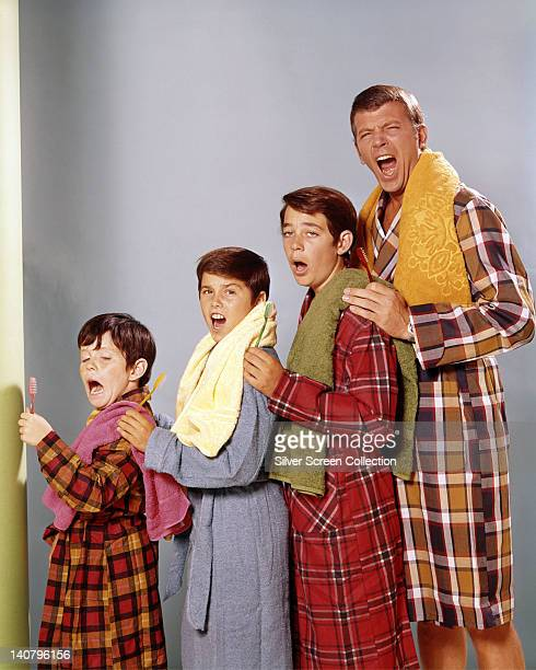 Mike Lookinland US child actor Christopher Knight US child actor Barry Williams US child actor and Robert Reed pose wearing bathrobes and holding...