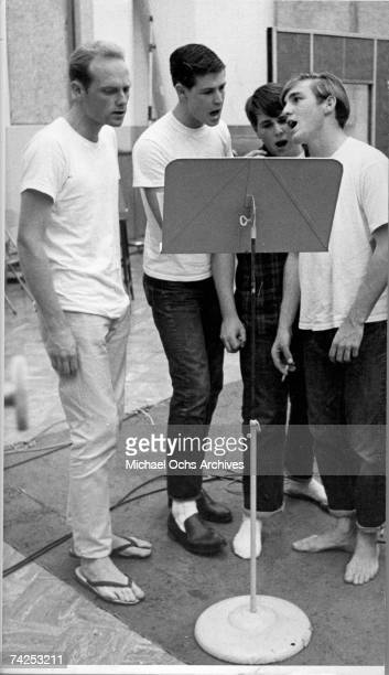 Mike Love Brian Wilson Carl Wilson and Dennis Wilson of the rock and roll band 'The Beach Boys' sing at a music stand in circa 1963