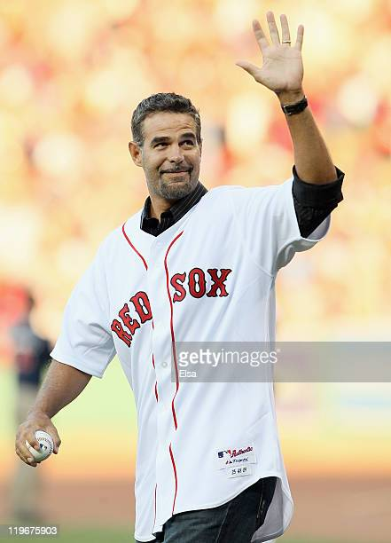 Mike Lowell former Red Sox third baseman waves to the fans as he heads out to the mound to throw a ceremonial first pitch before the game against the...